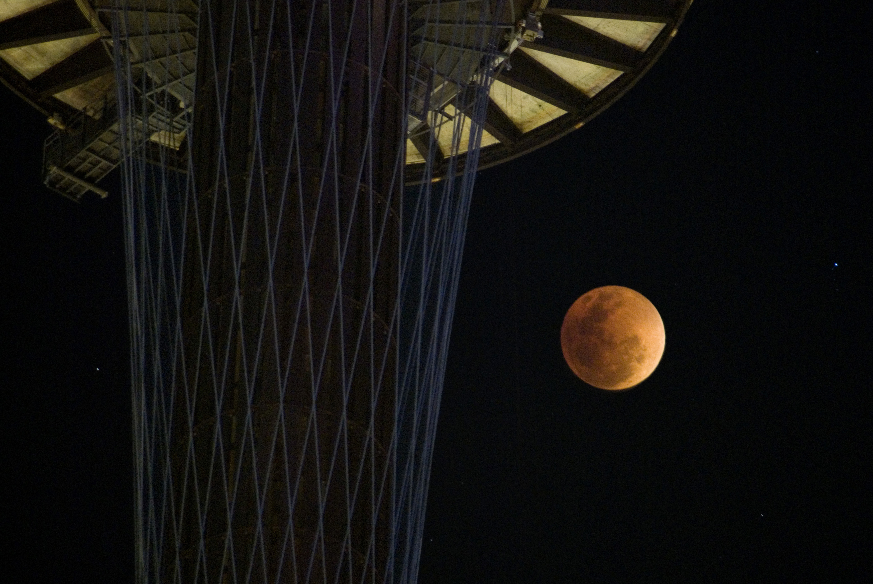 Beautiful copper colored full moon in a night sky during an eclipse pictured against the sydney tower