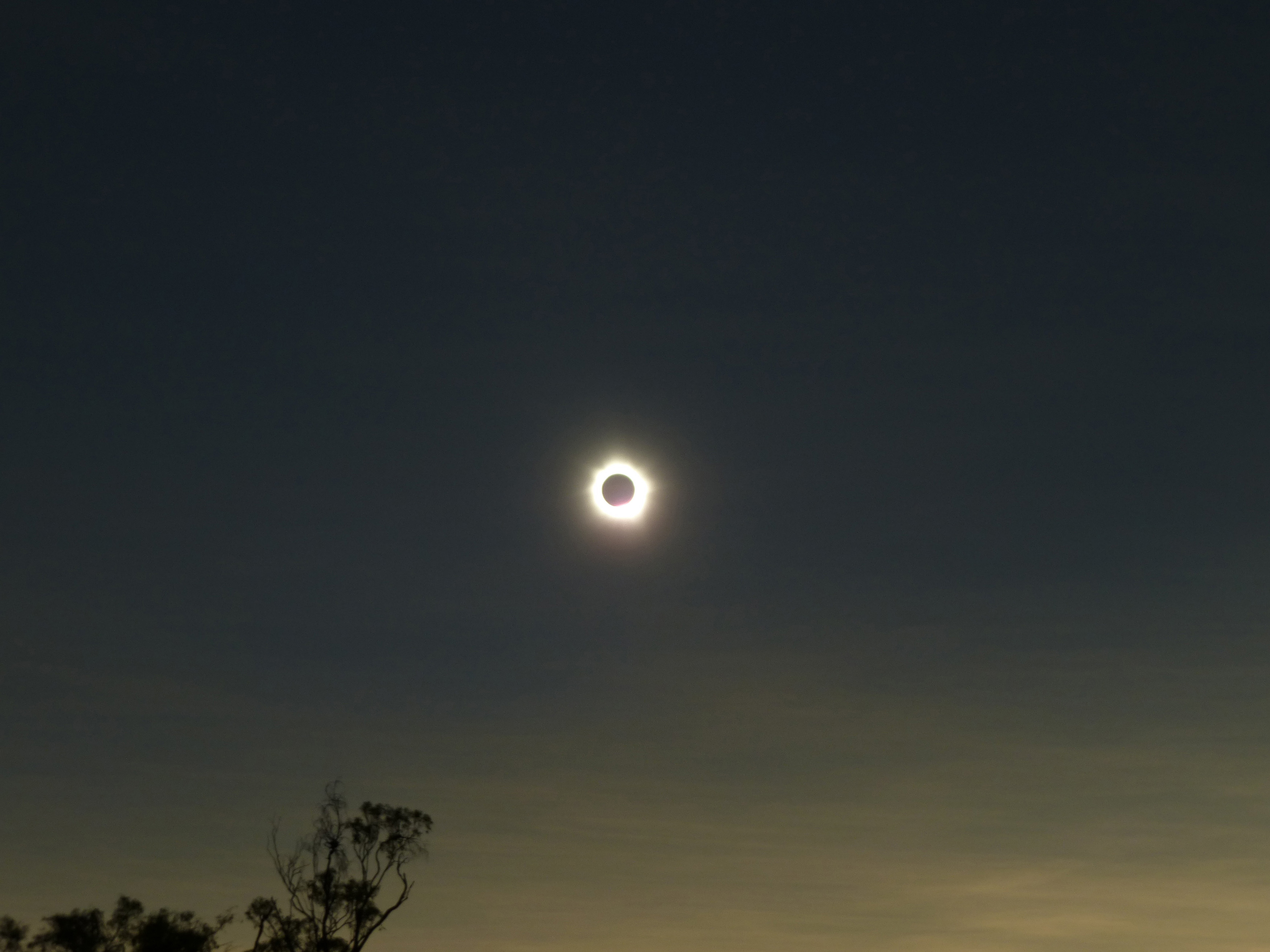 Solar eclipse with corona in a darkened sky as the moon passes between the sun and the earth obscuring the sun