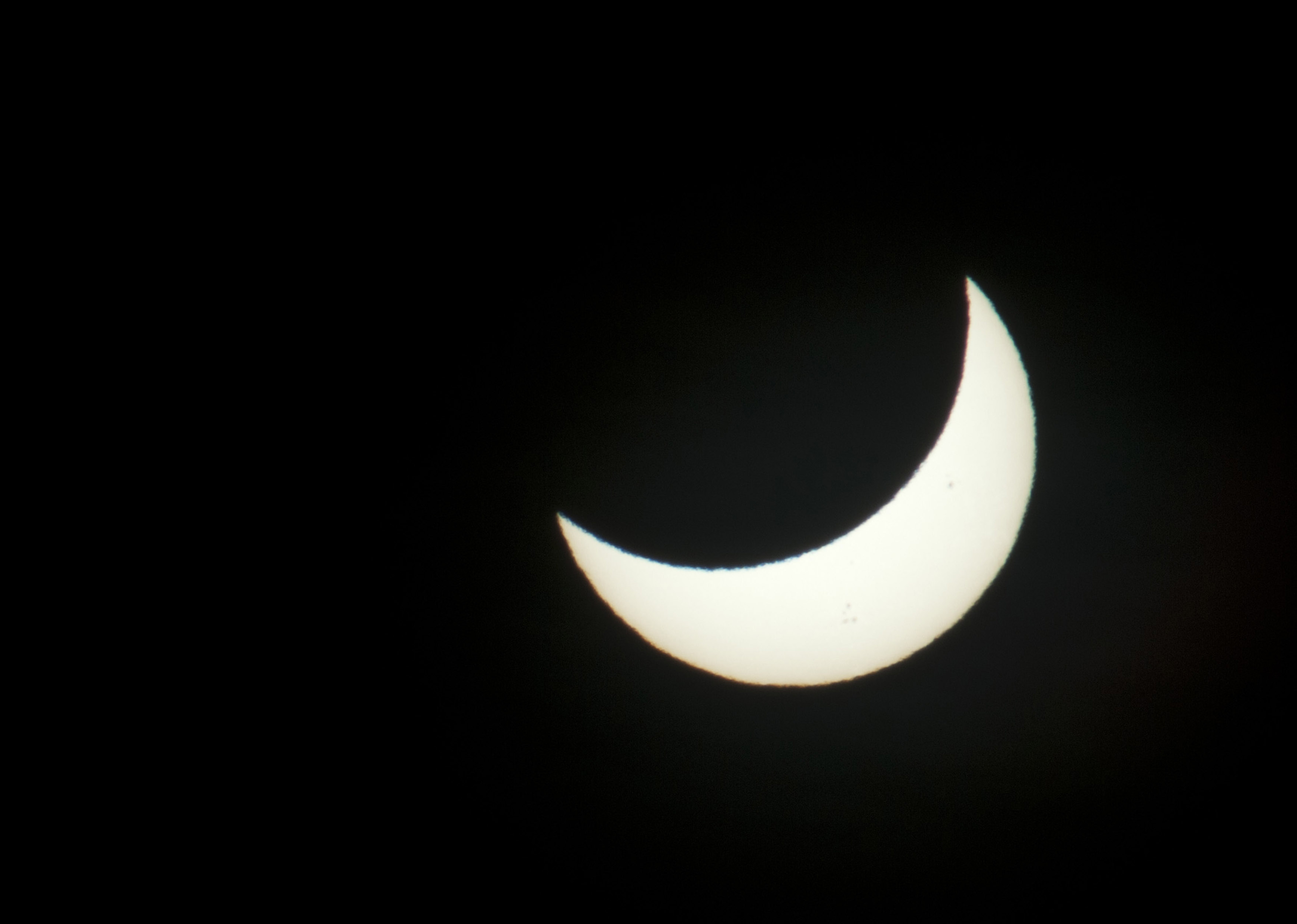 The sun as pictured through a dark filter during a solar eclipse, partially blocked by the moon