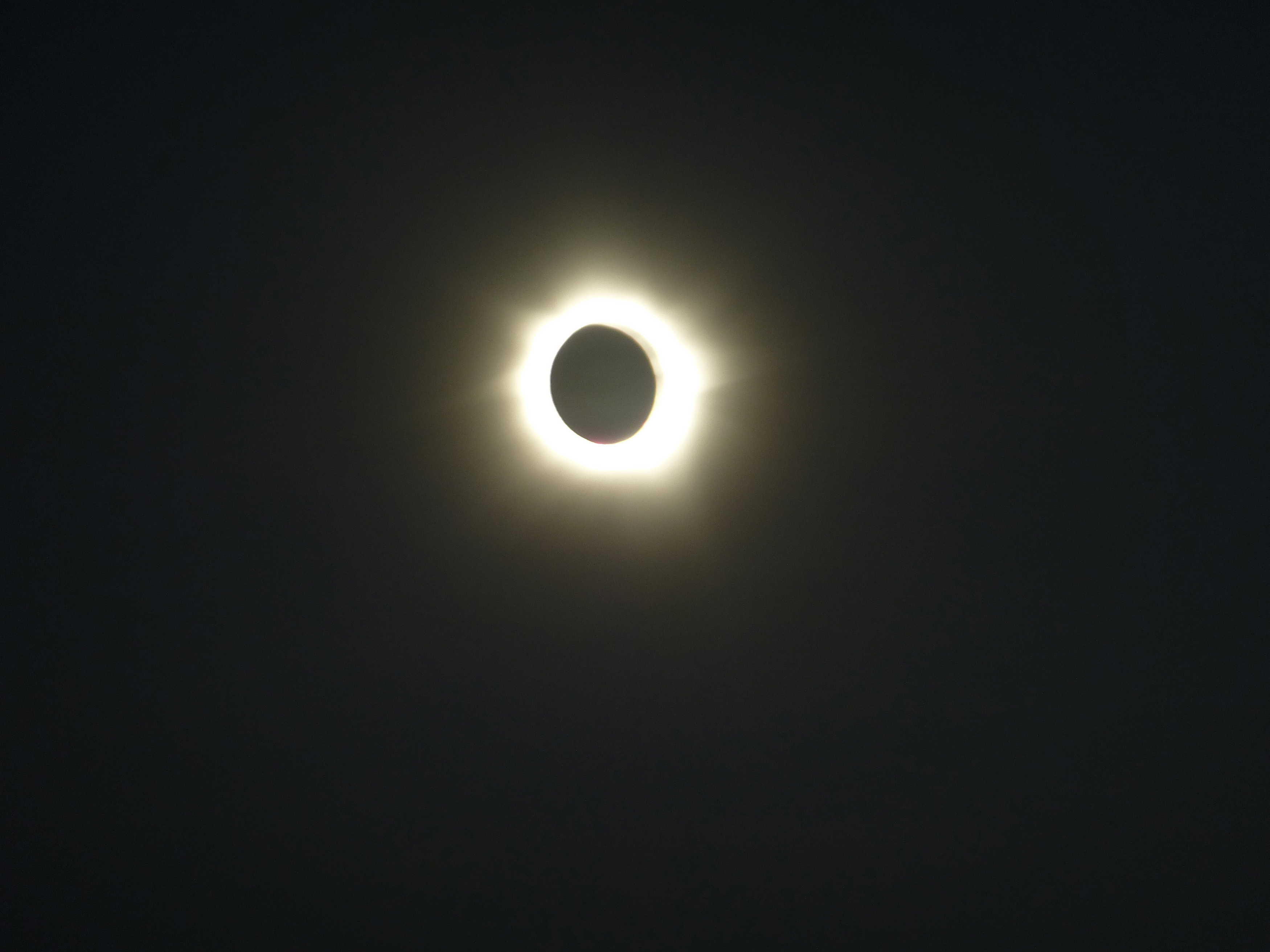 Solar eclipse in a darkened sky with the corona of the sun shining out around the moon as a bright halo