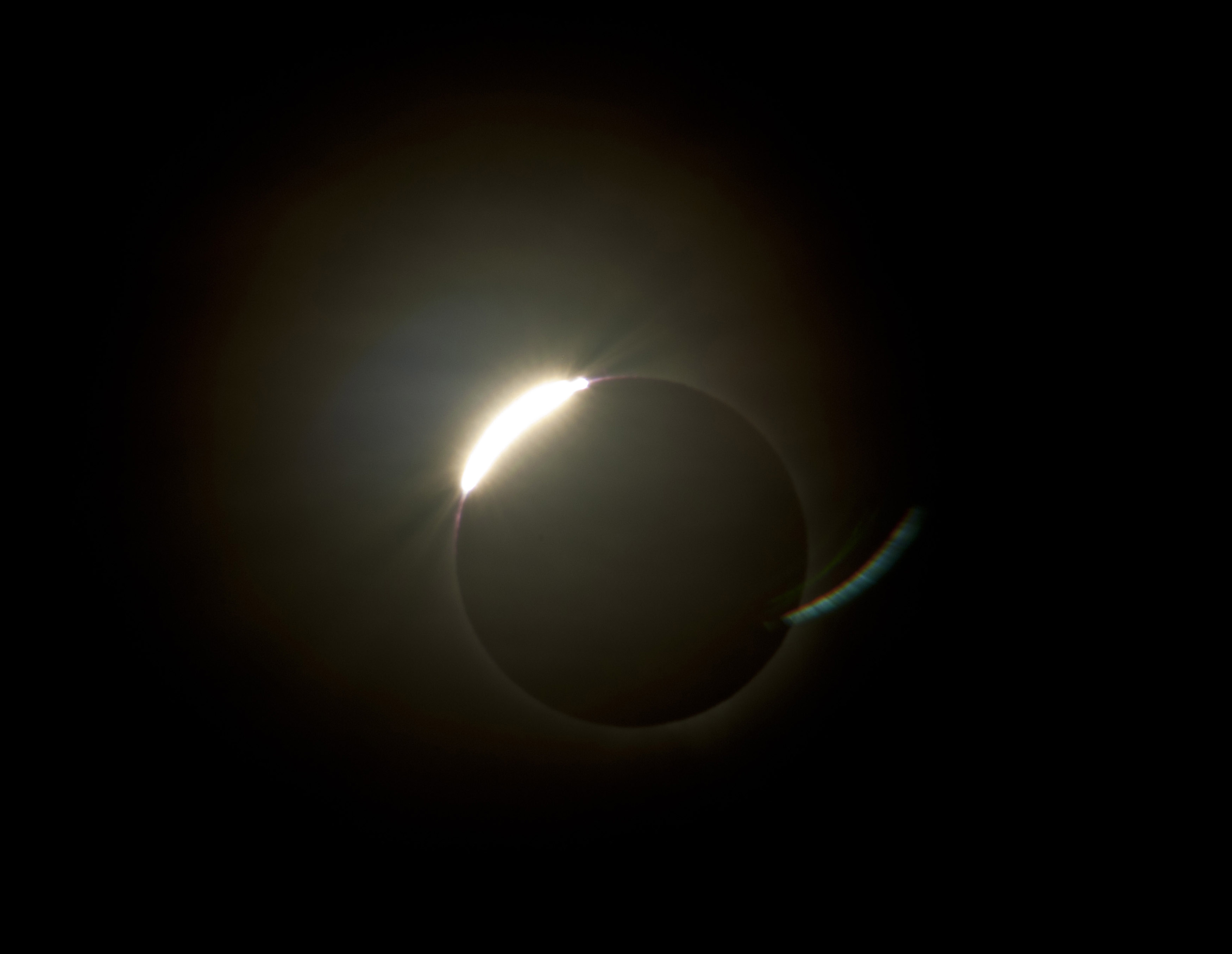 The sun emerging from behind the moon during a total solar eclipse with a ring of illumnated corona still visible