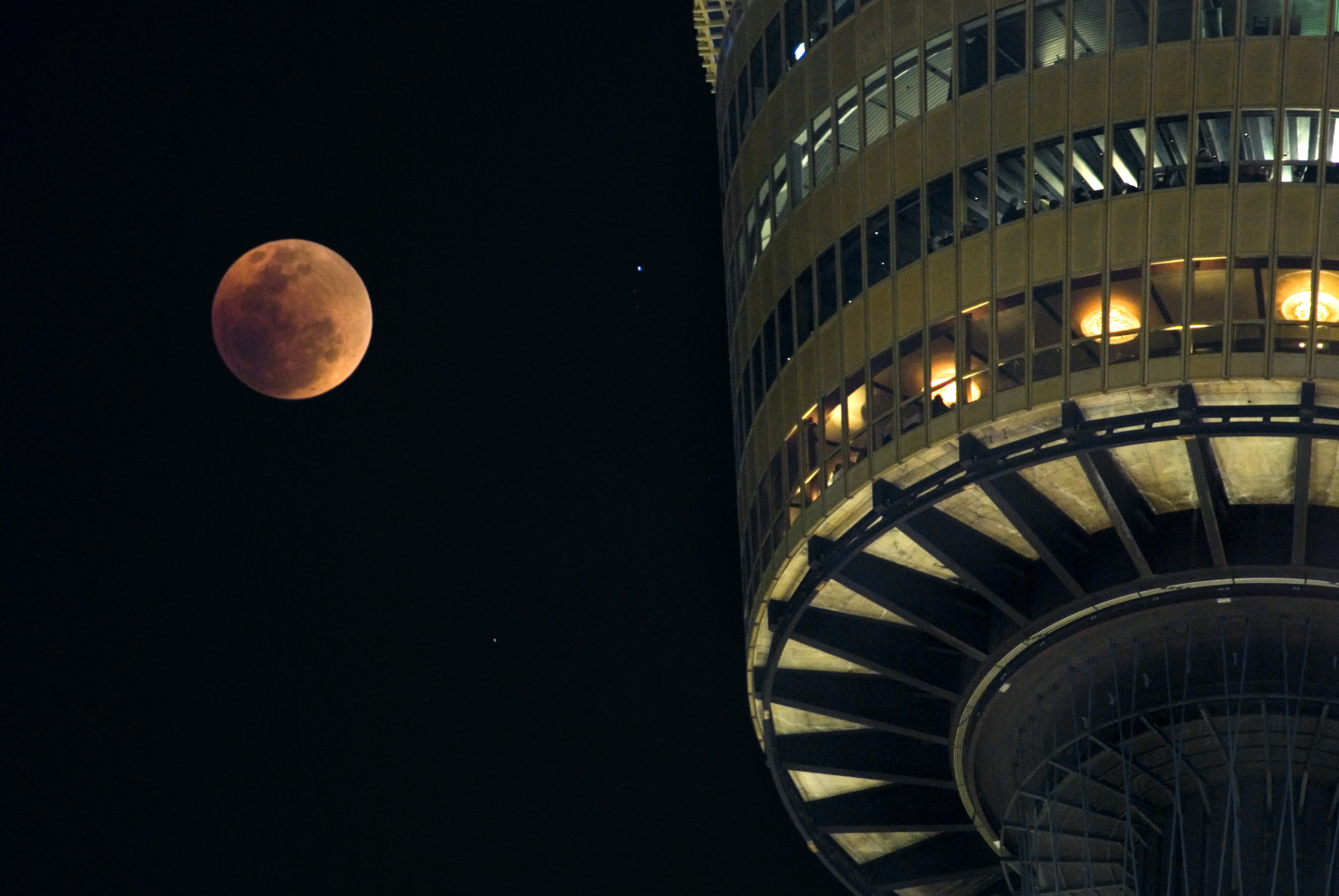 Lunar eclipse in a dark sky with a red colored full moon alongside an illuminated tower observsatory