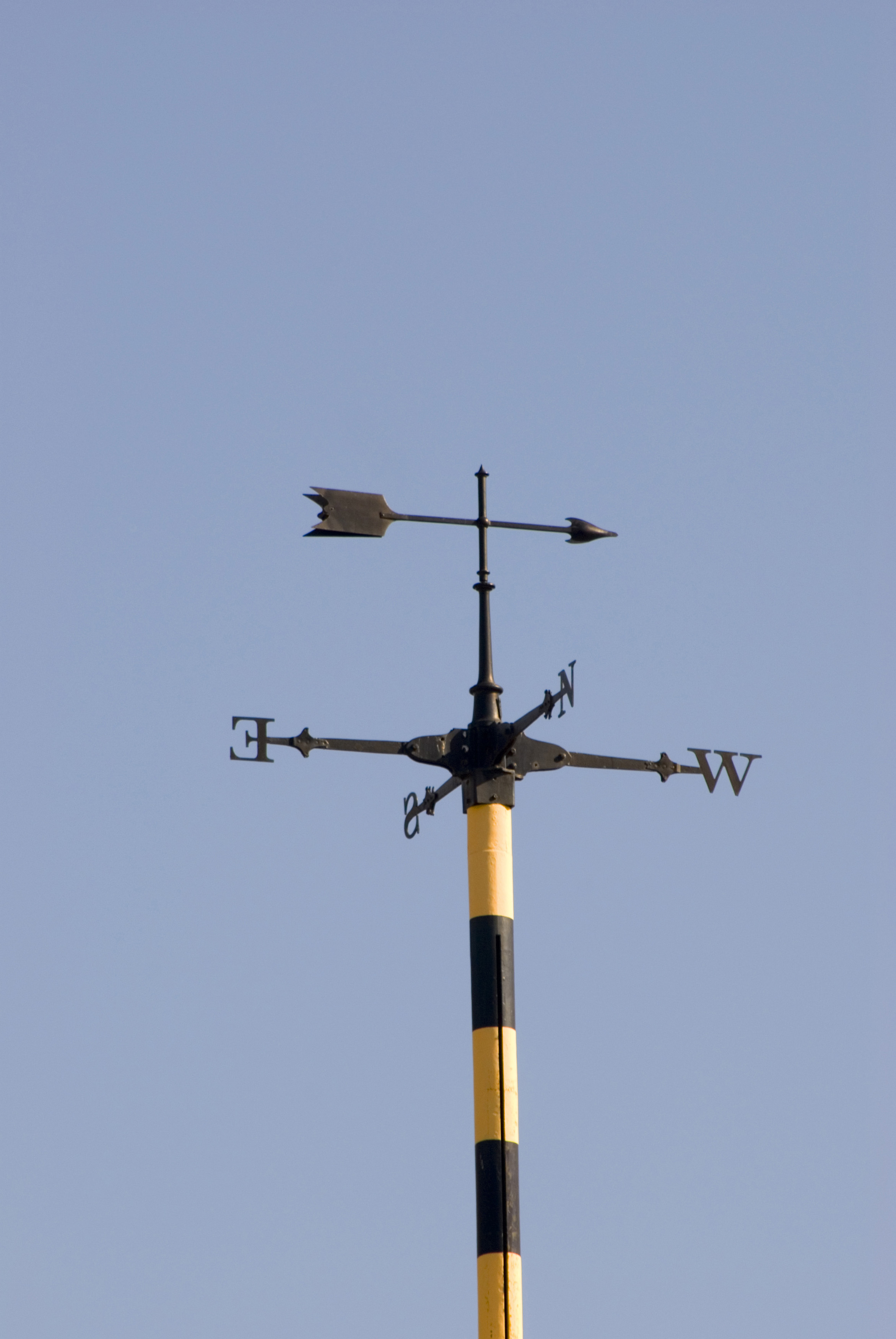 Weather vane with an arrow showing the wind direction and the four points of the compass below against a clear blue sky, this vane was located at the top of an observatory after 1pm when the time ball had fallen to the bottom of the mast