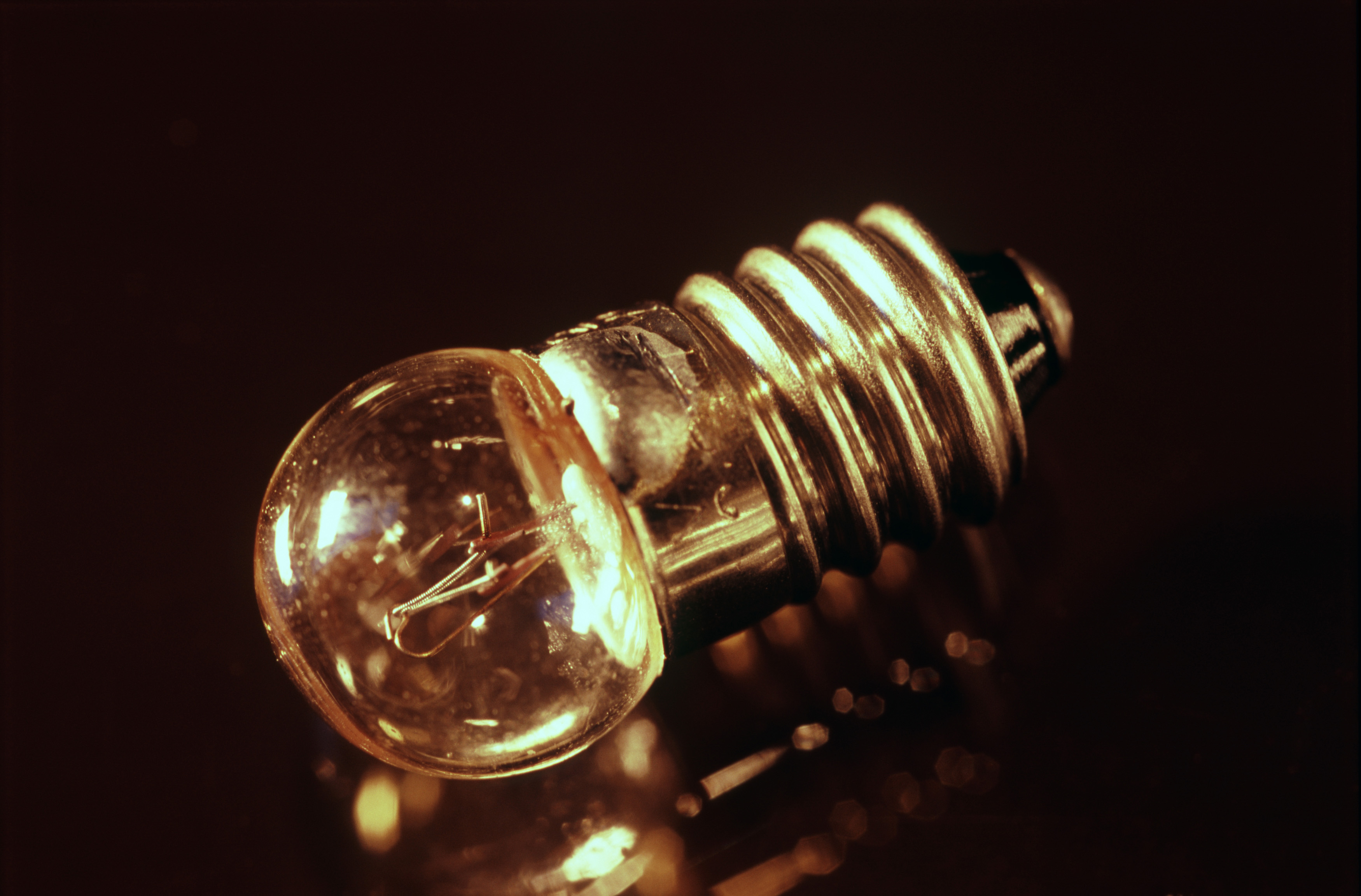 Small light bulb for a torch or flashlight with a screw thread on a dark reflective surface