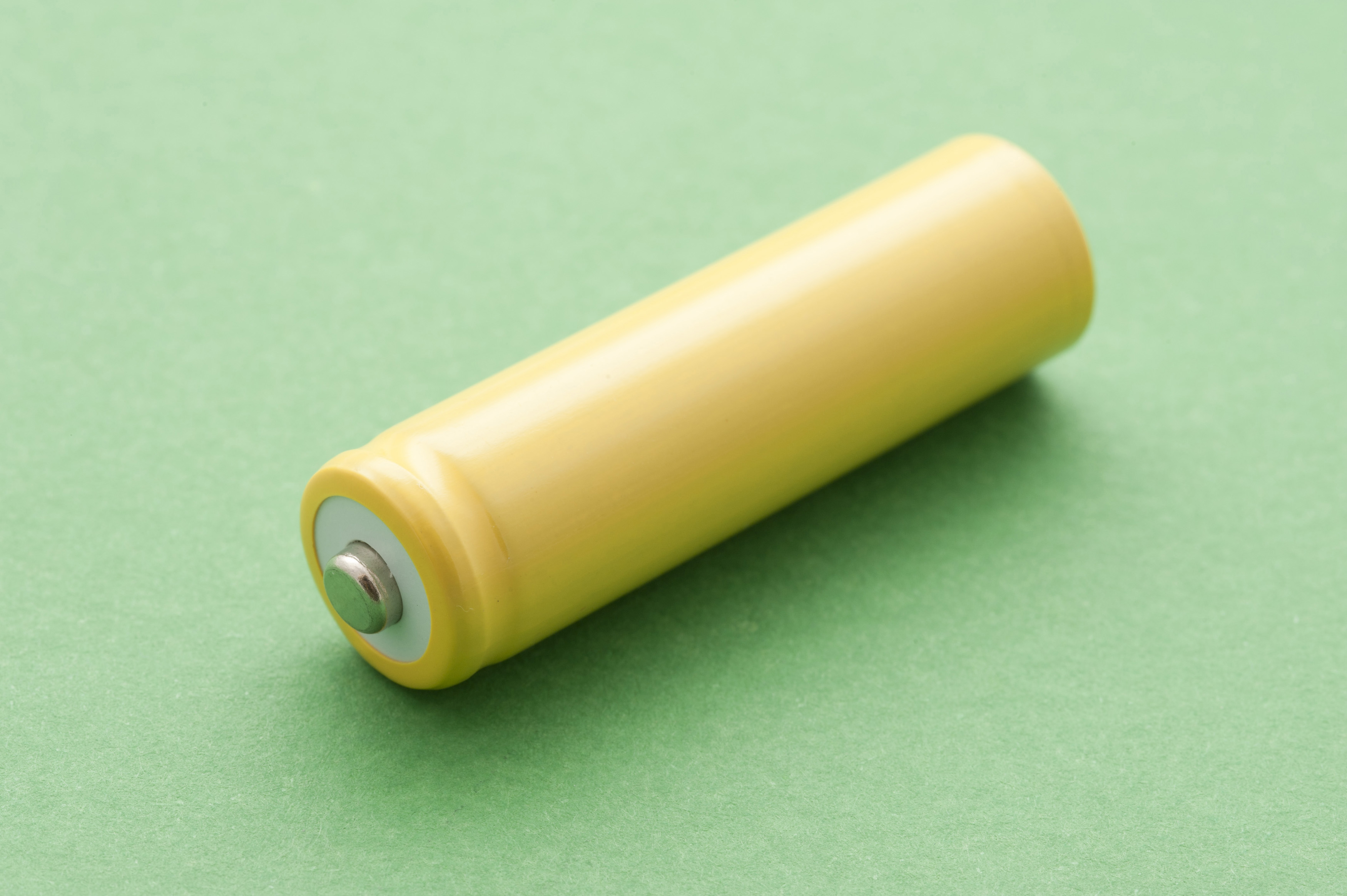 Single yellow unlabelled battery lying diagonally on a green background used to generate electricity from chemical energy