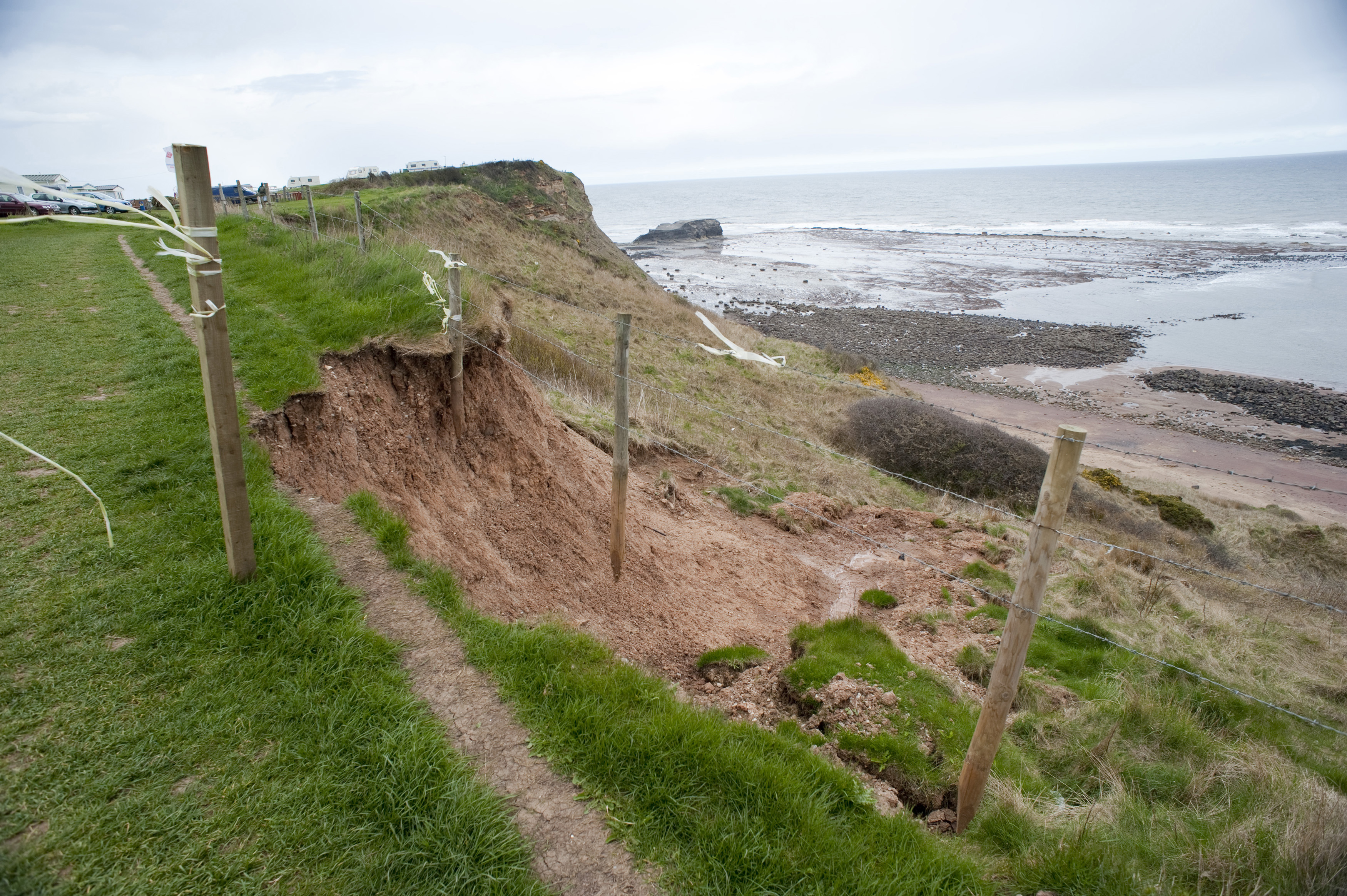 Soil erosion and washaway on a coastal cliff with landslip caused by weathering and water