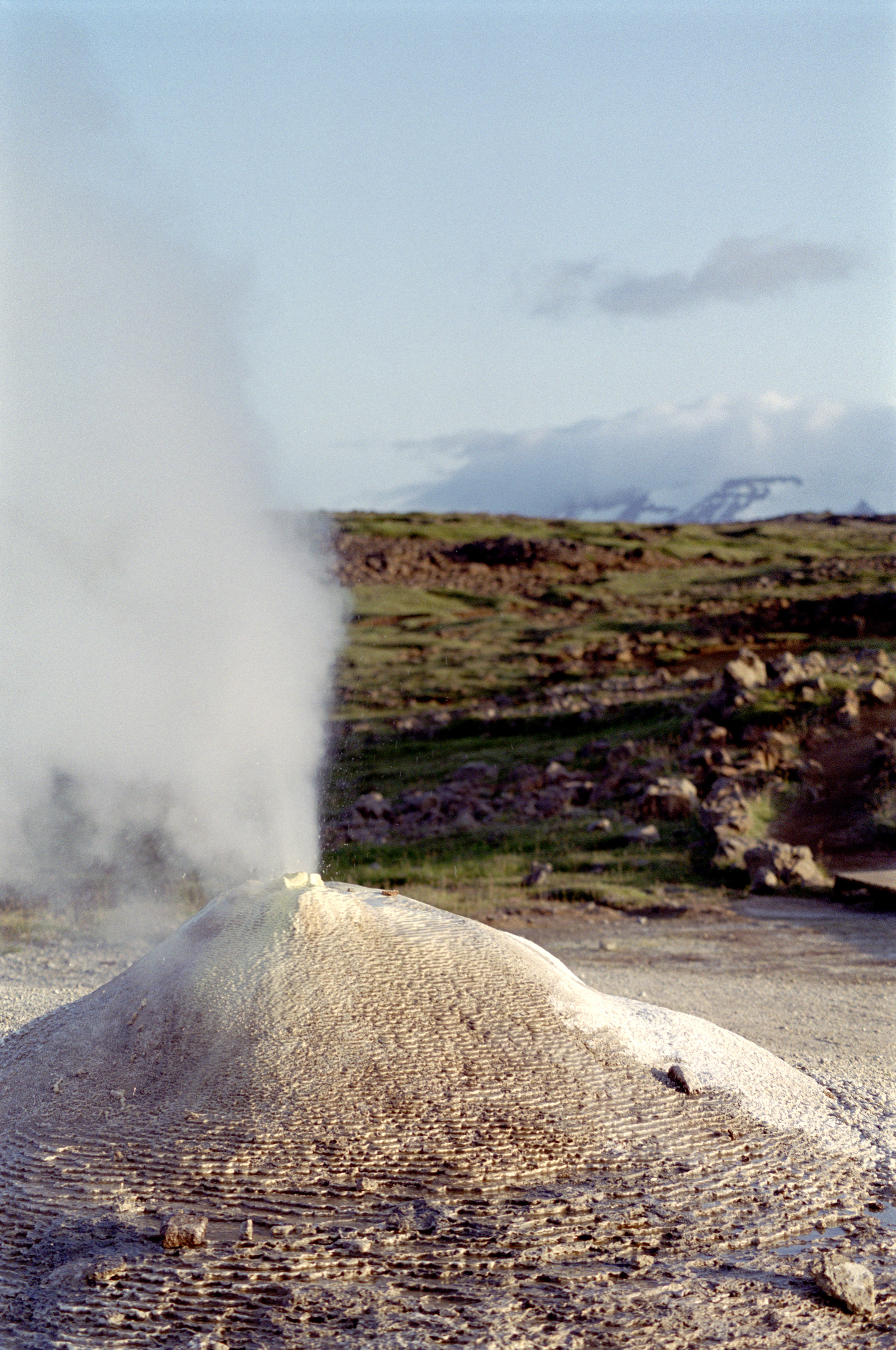 Steam ejecting from the top of a mound around the mouth of a geyser, a natural hot spring that releases pressure by releasing a column of water and steam