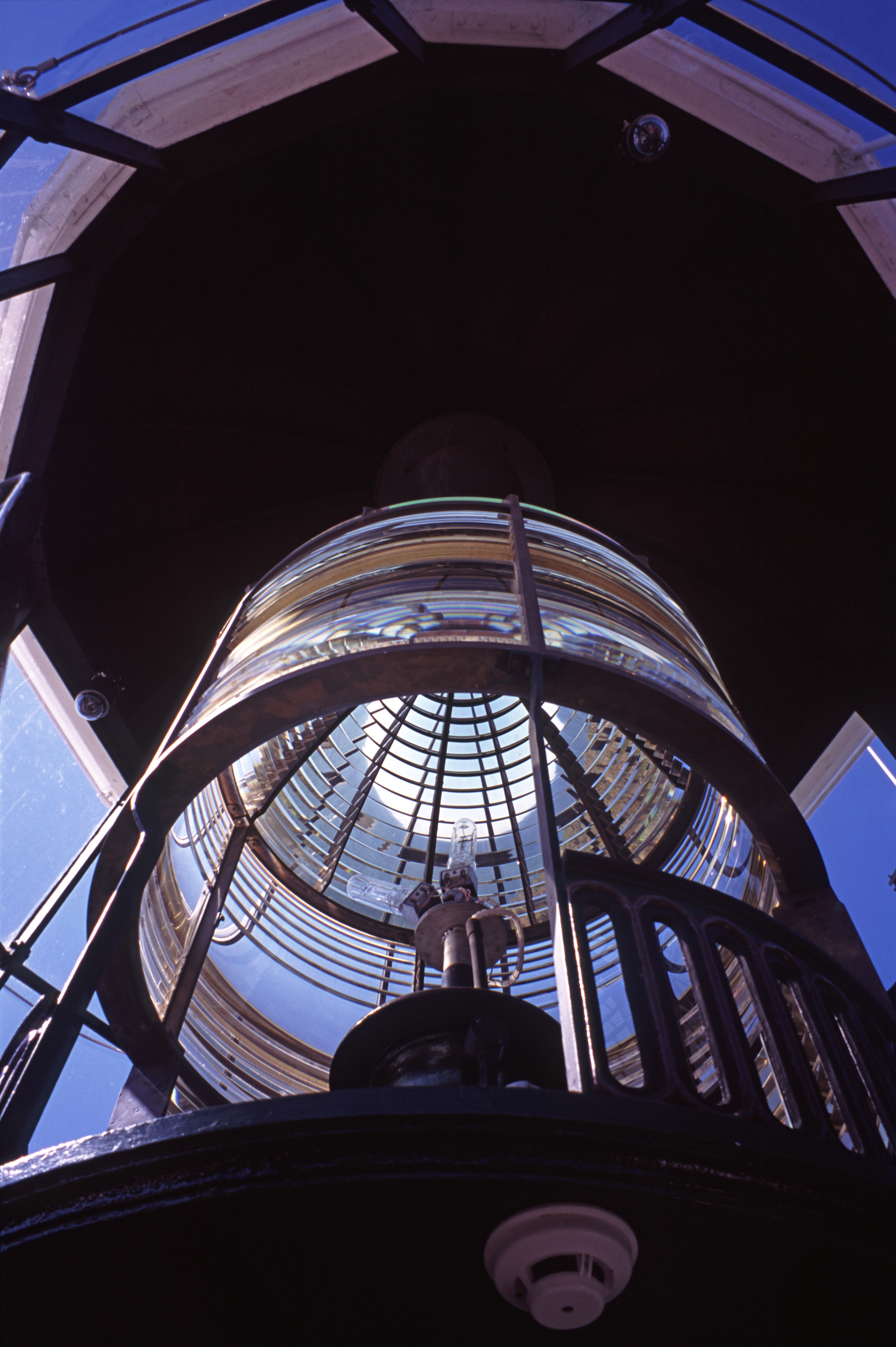 a low angle view of the complex lens and lighting system in a lighthouse lantern room.