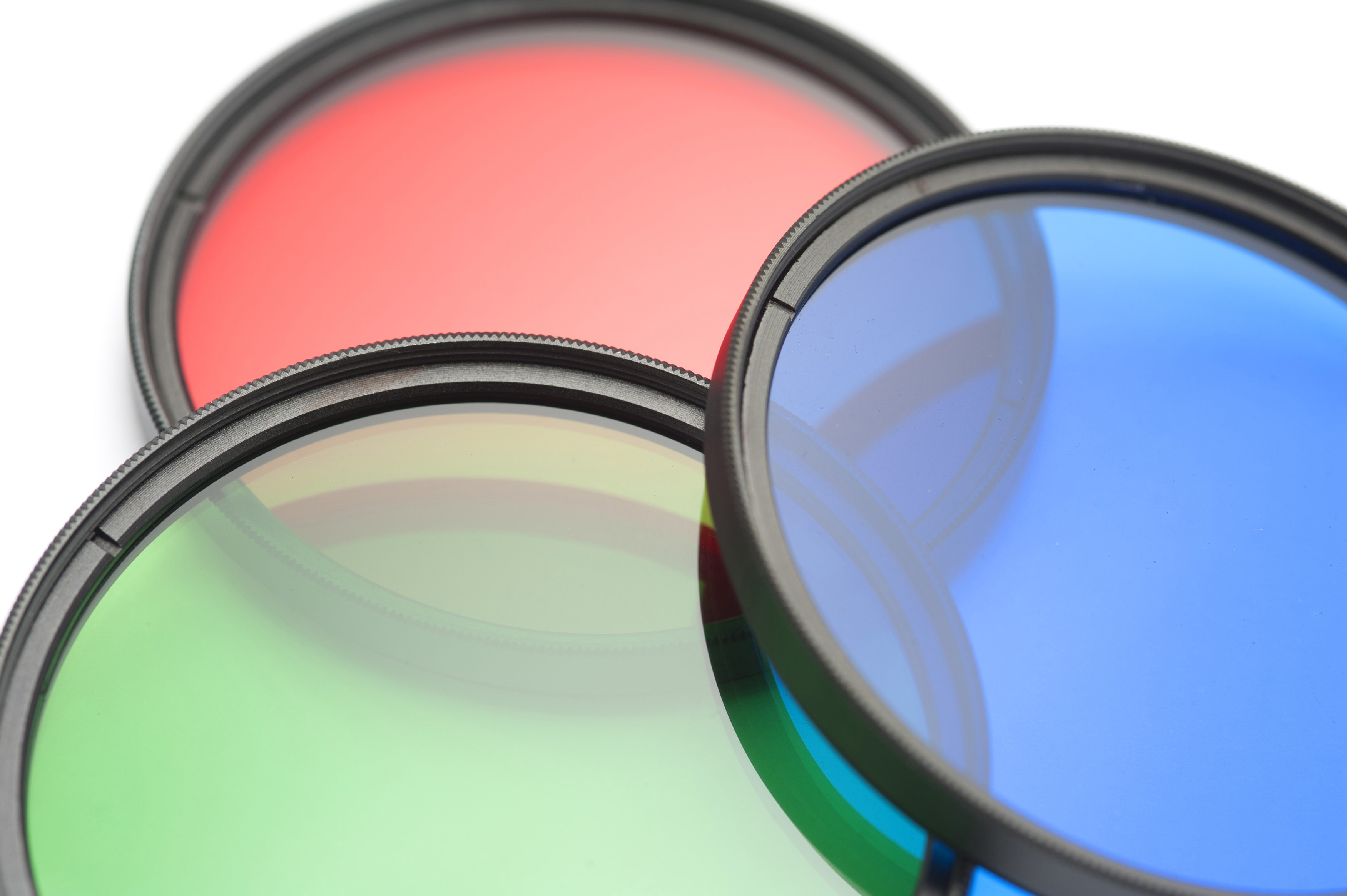 Set of circular filters showing the primary colors red, green and blue arranged to overlap on a white background, close up view