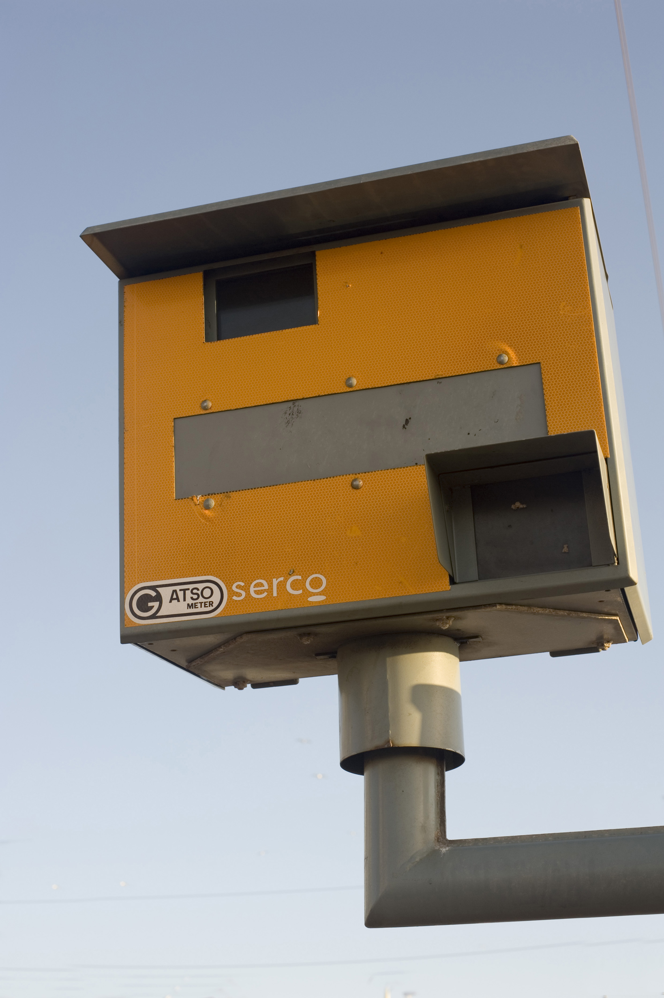 Yellow speed camera mounted on a pole overlooking a road to clock and photograph speeding motorists as they drive by in their cars, the camera uses a radar system the detect the speed of the motorist