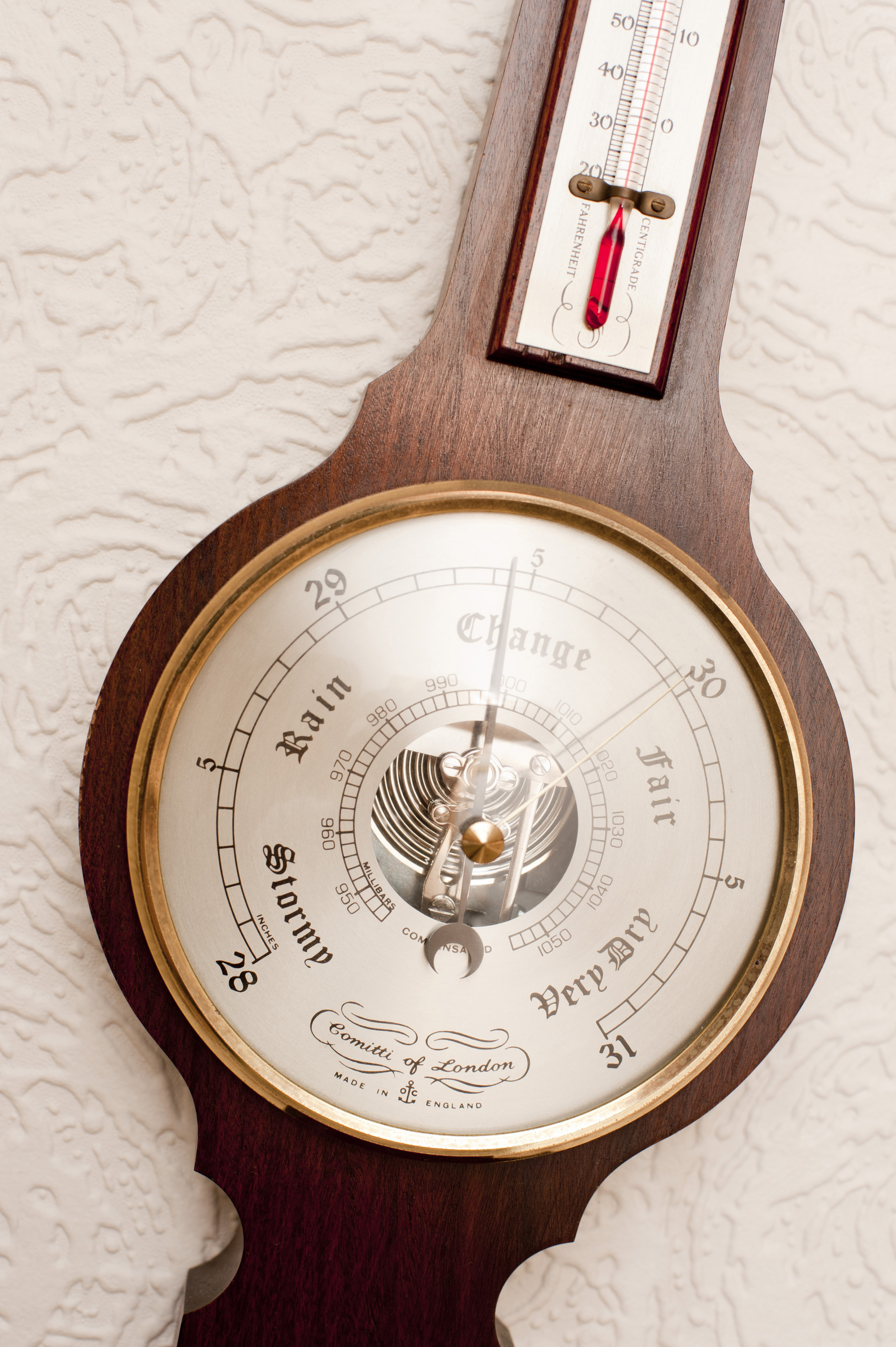Modern aneroid barometer for measuring changes in atmospheric pressure resulting in changes in the weather, close up detail of the glass dial and needle