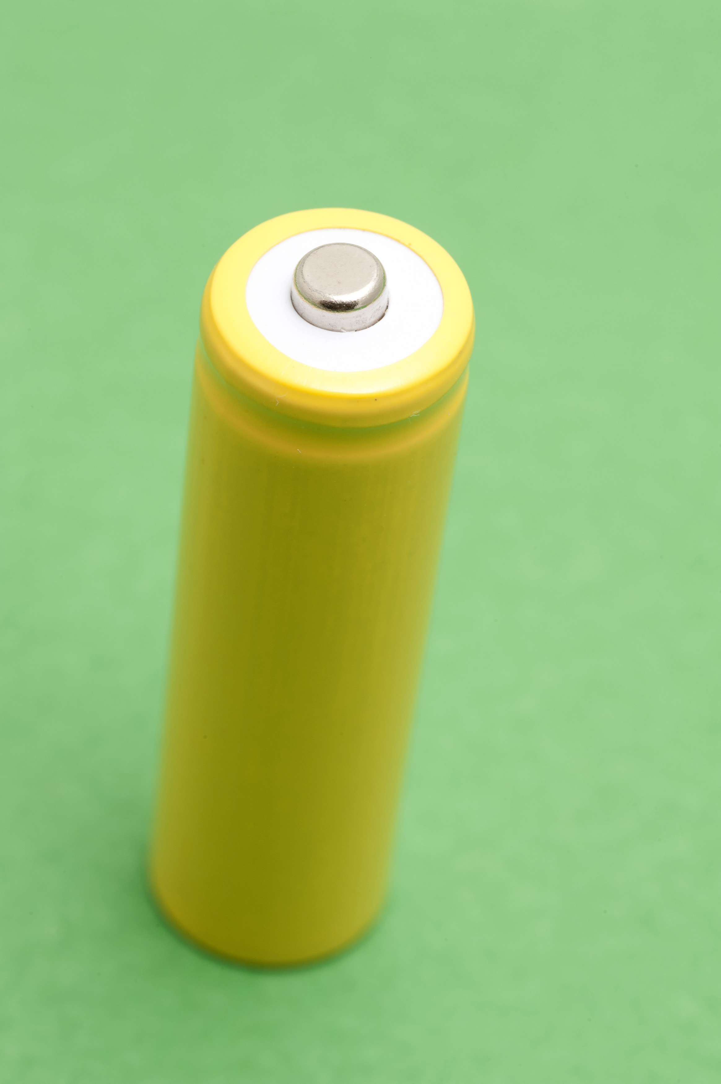 view of the positive terminal on a single unlabeled yellow battery cell on a green background