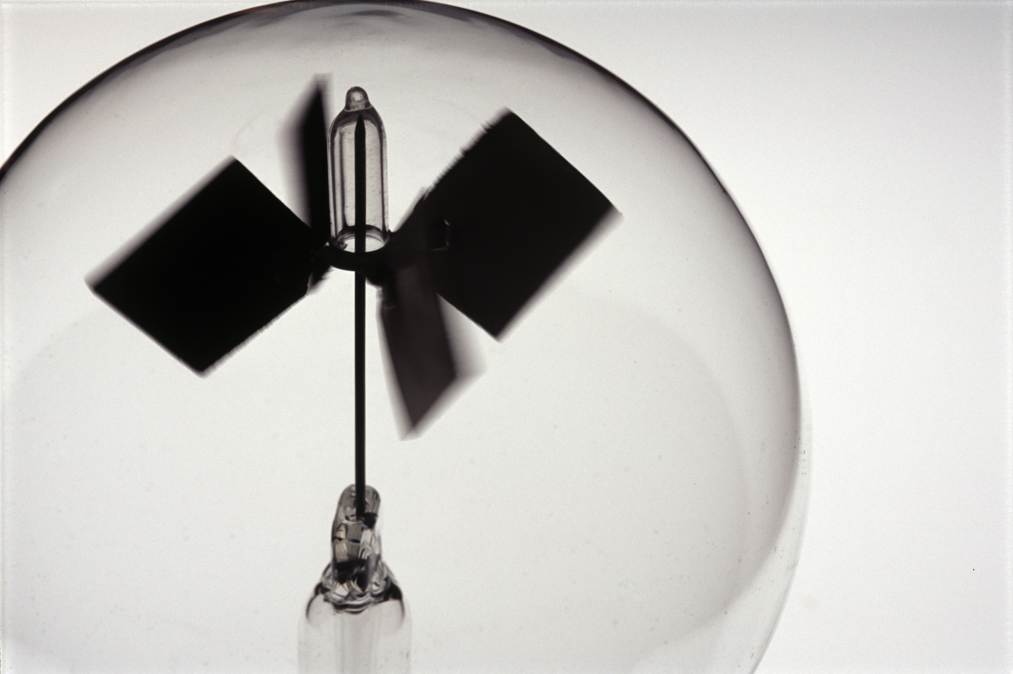 silhouette image of a light mill, a partially evacuated flash sphere with white and black painted light vanes inside which spin when light radiation falles on them