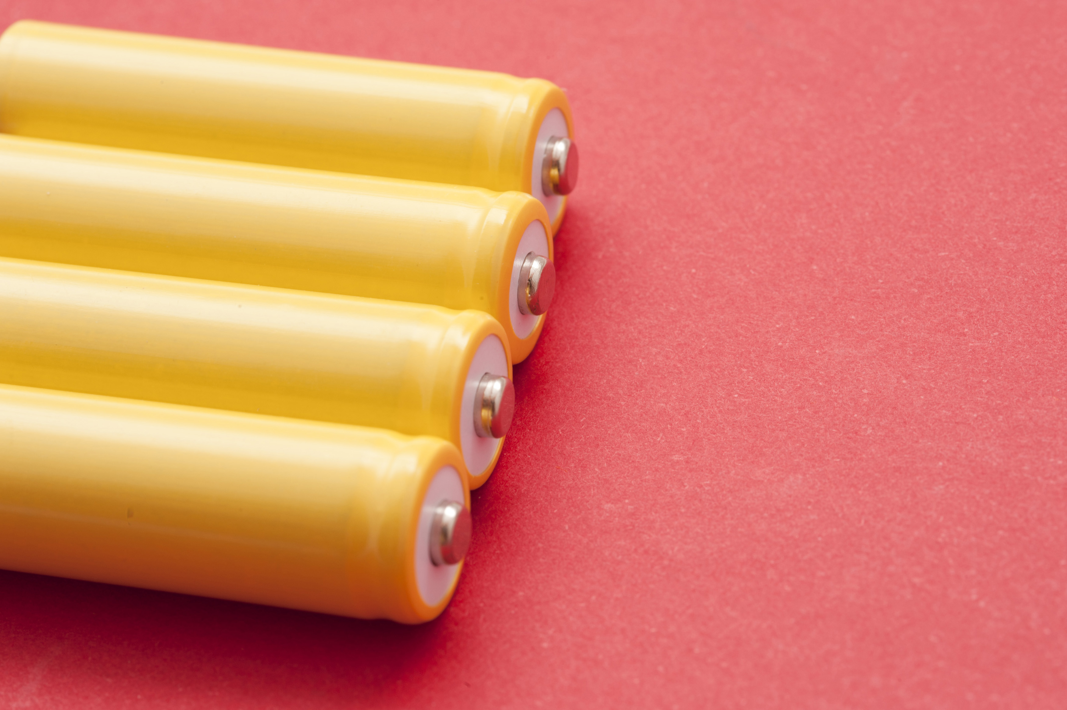 Set of four yellow unlabeled batteries lying in a row on a red background with copyspace